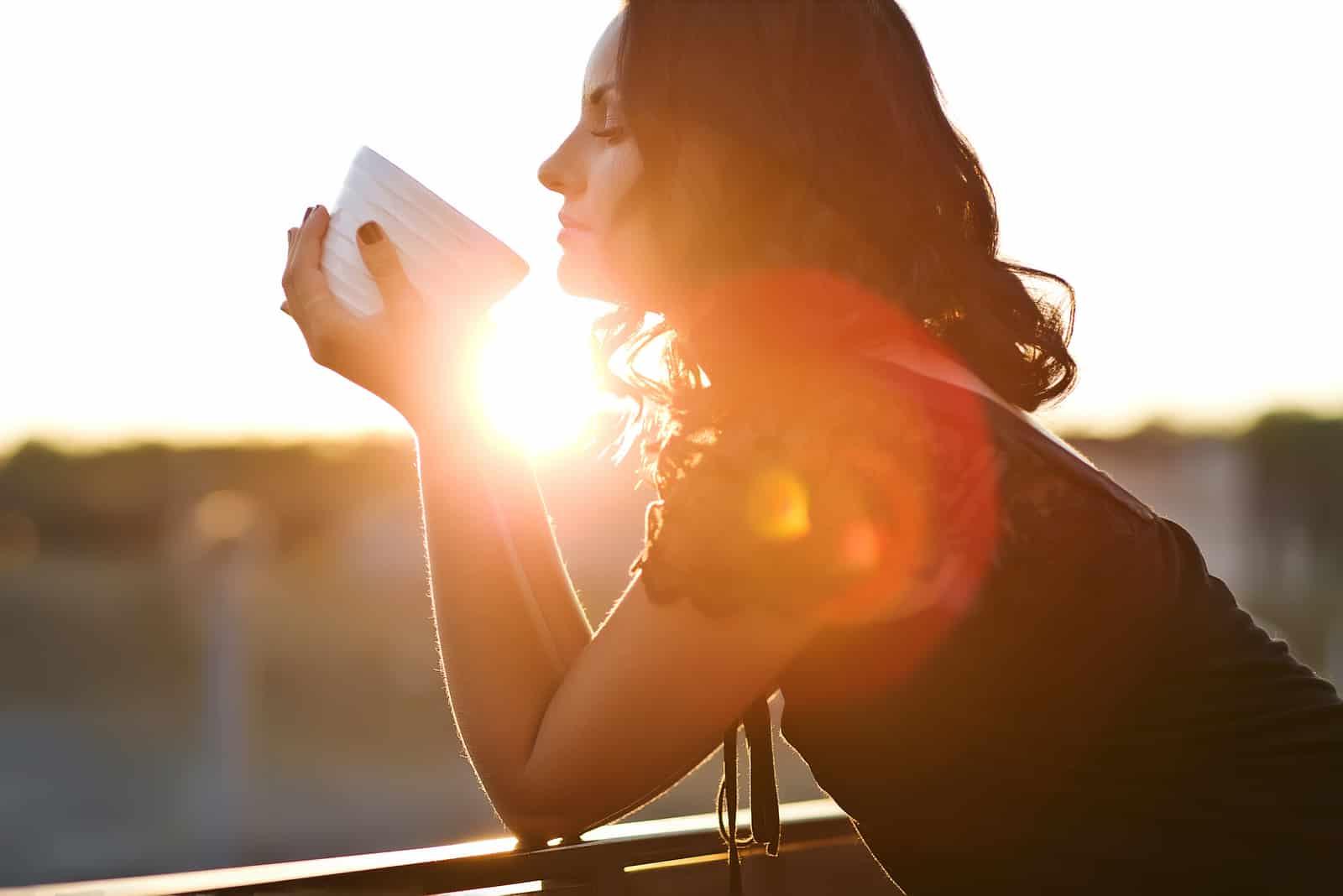 Femme buvant du café en plein air dans la lumière du soleil