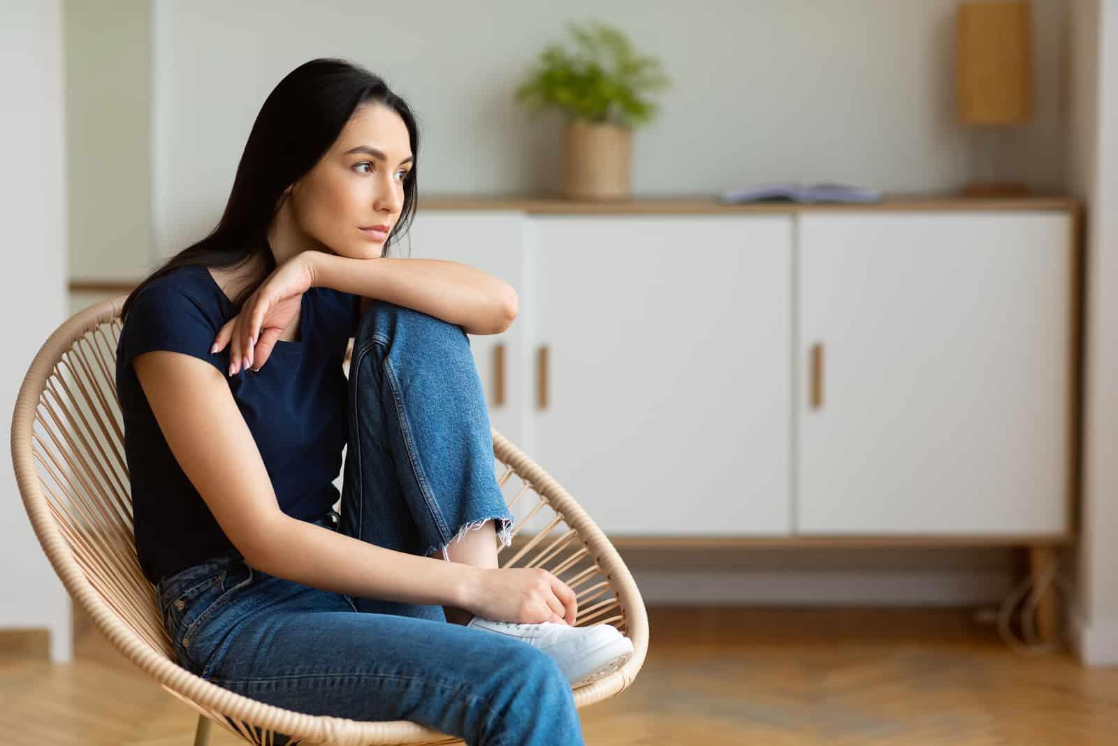 Femme pensée séance dans fauteuil moderne