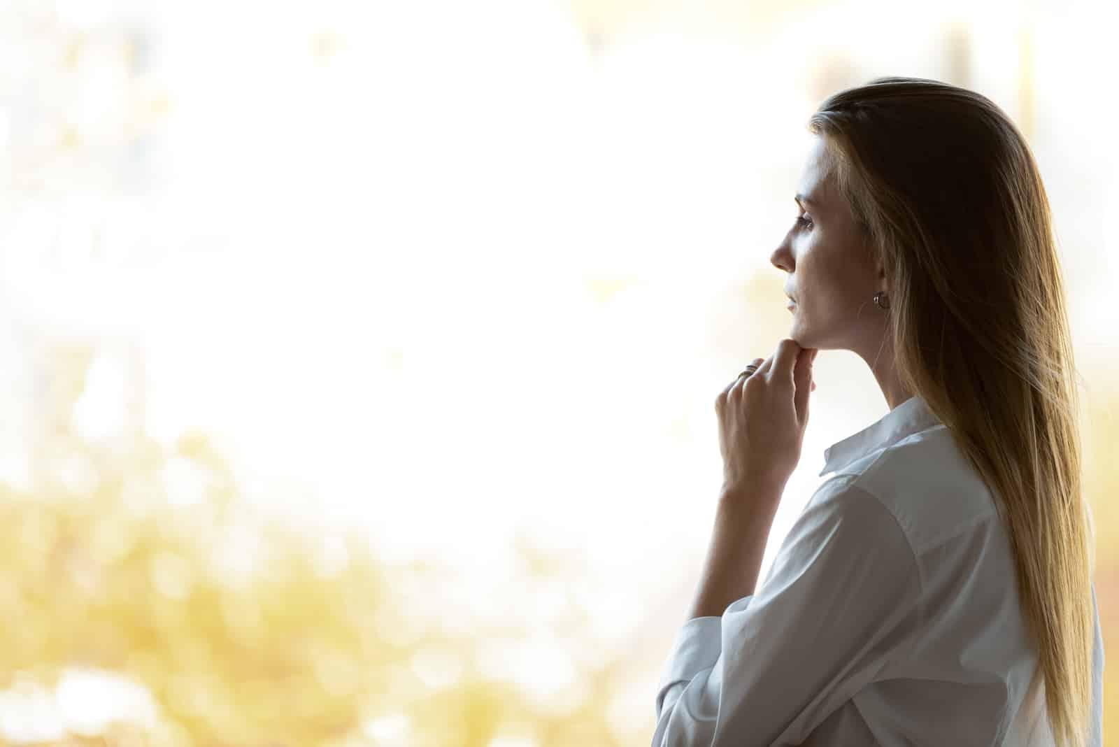 Femme regardant à travers la pensée de verre de fenêtre de bureau