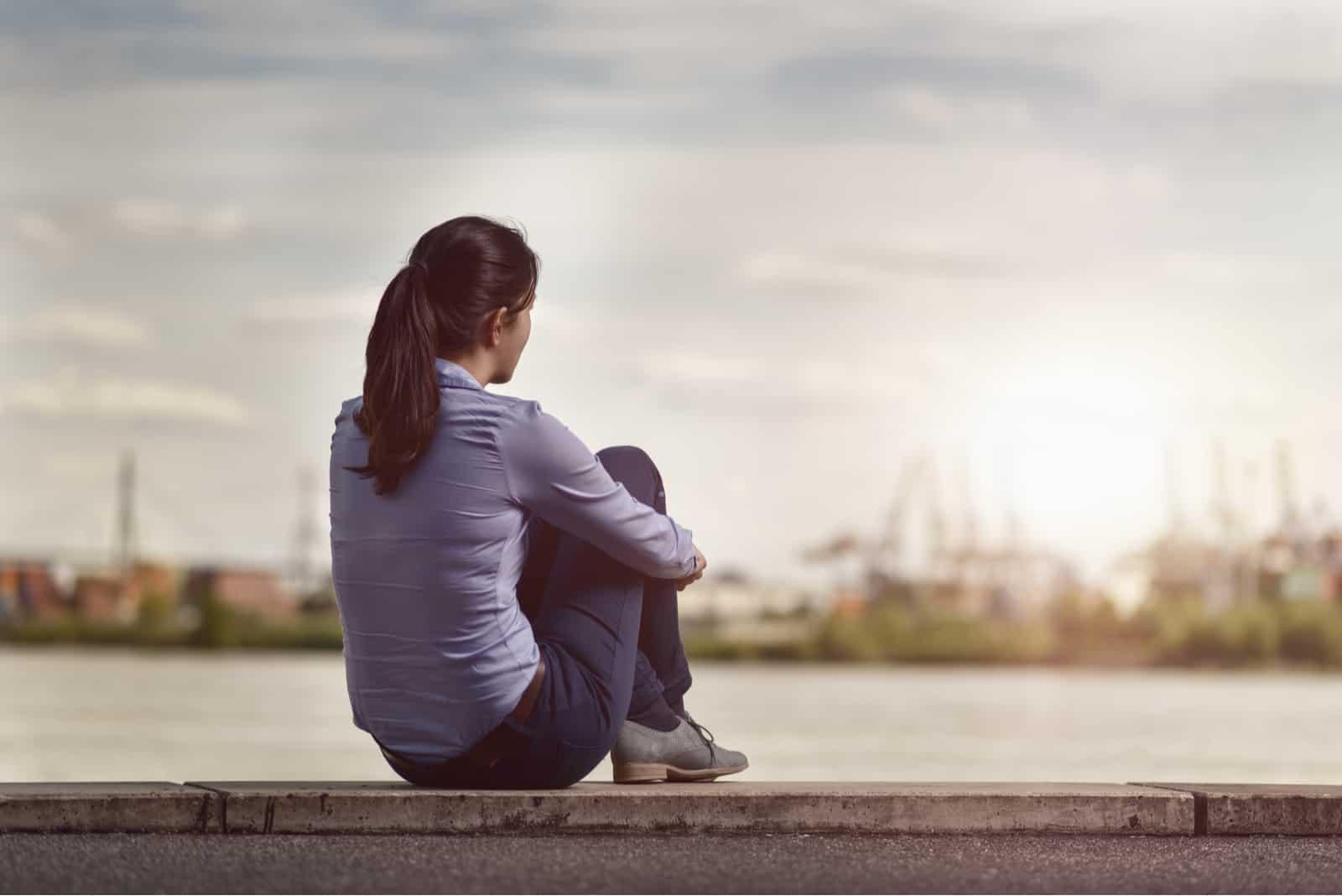 Femme regardant la rivière en position assise