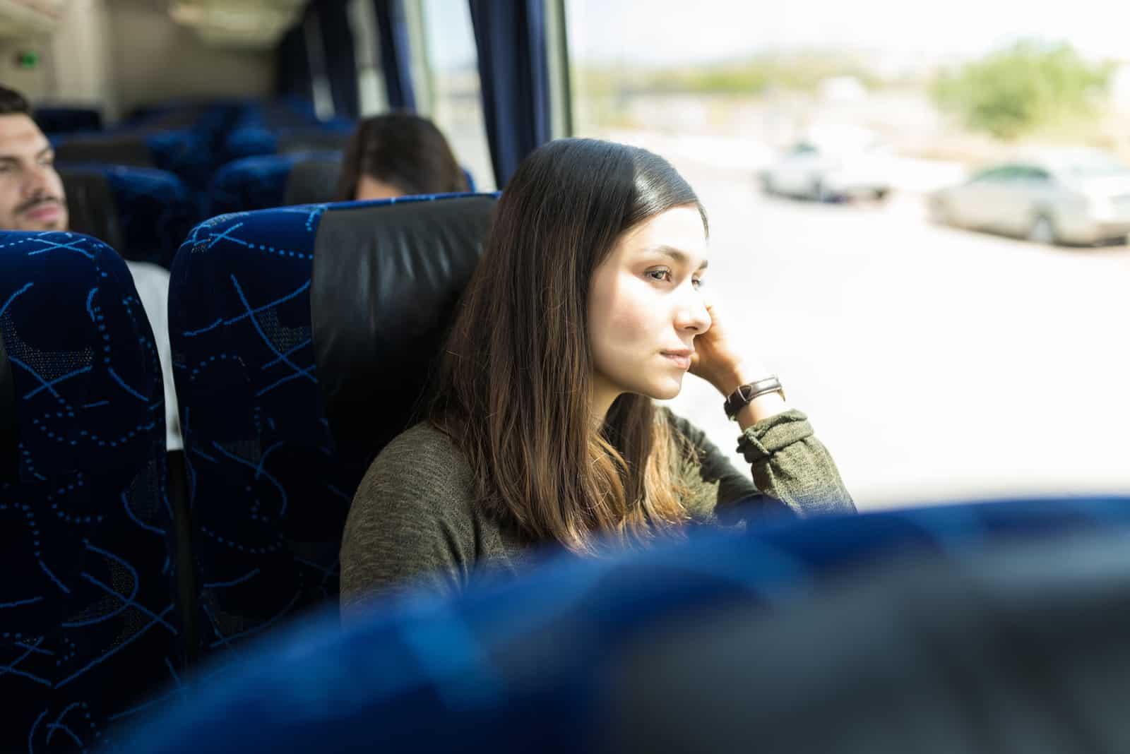 Femme regardant par la fenêtre lors d'un voyage en bus