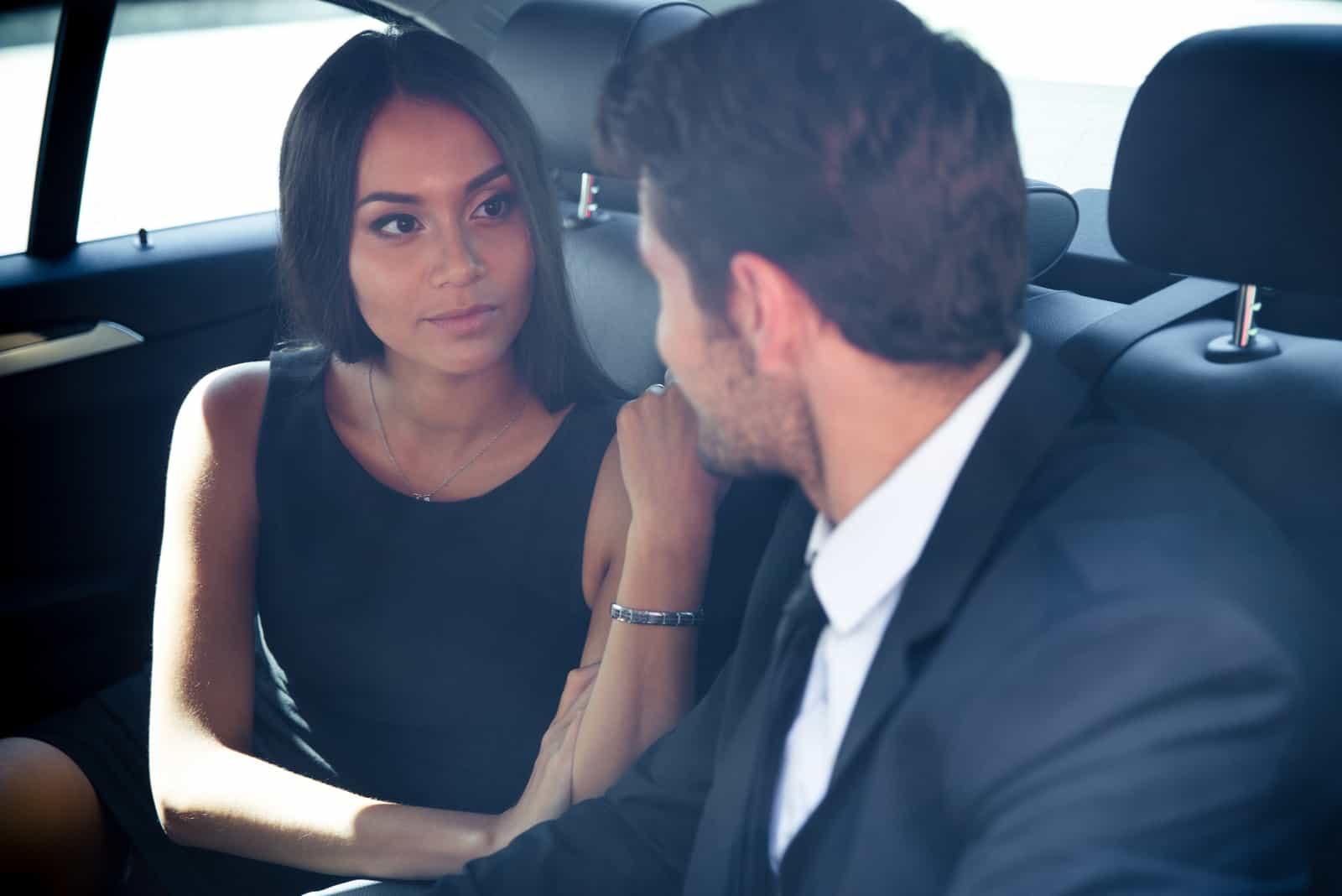 Homme affaires et femme affaires conversation dans siège arrière de voiture