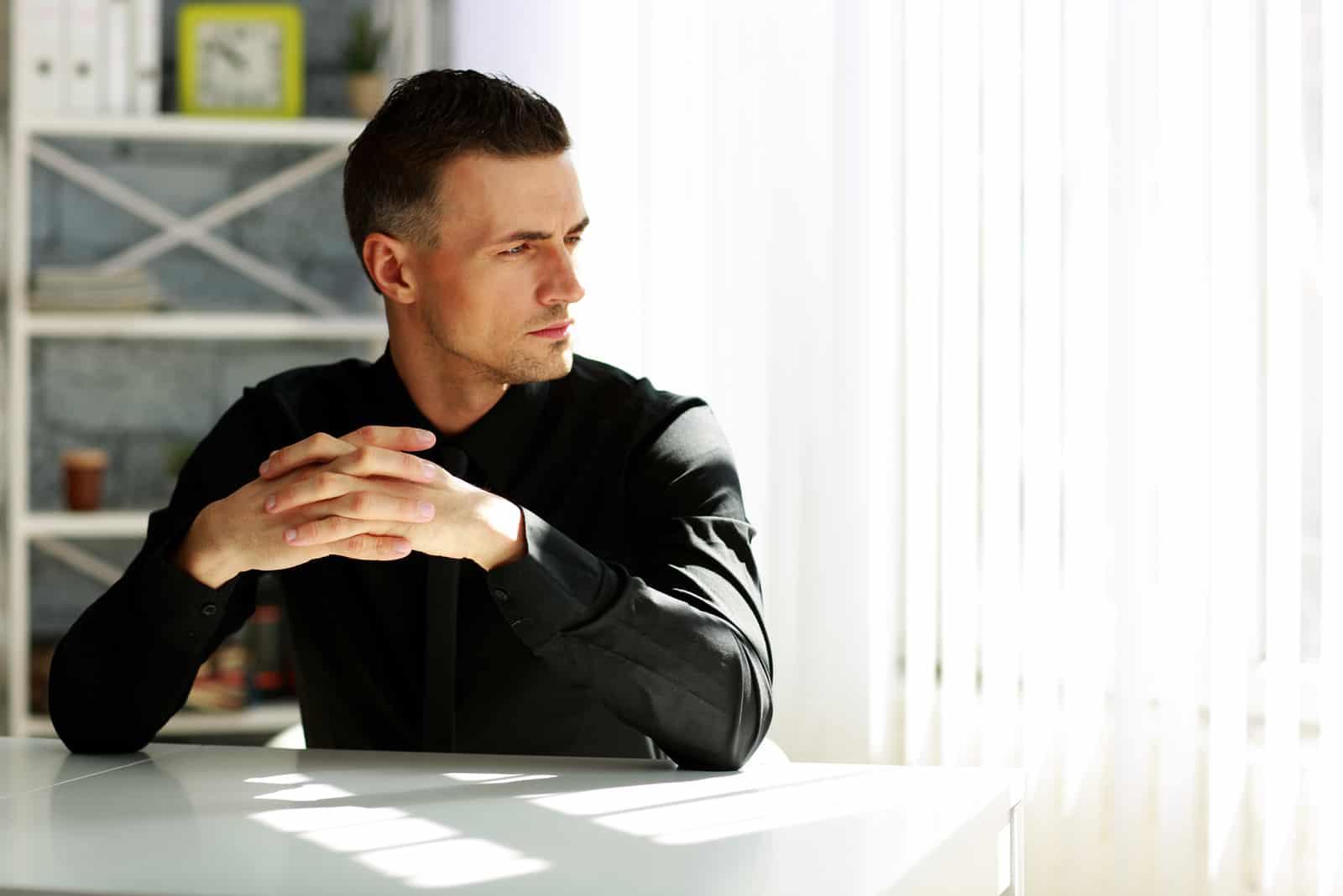 Homme d'affaires pensif assis à la table au bureau