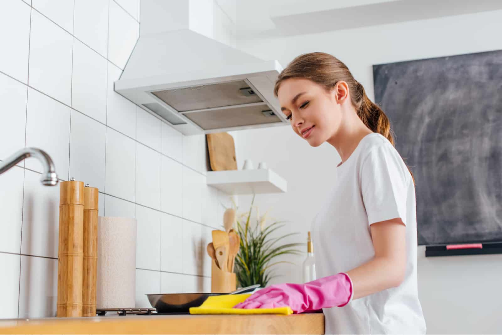 Jeune femme cuisine propre avec gant à portée de main