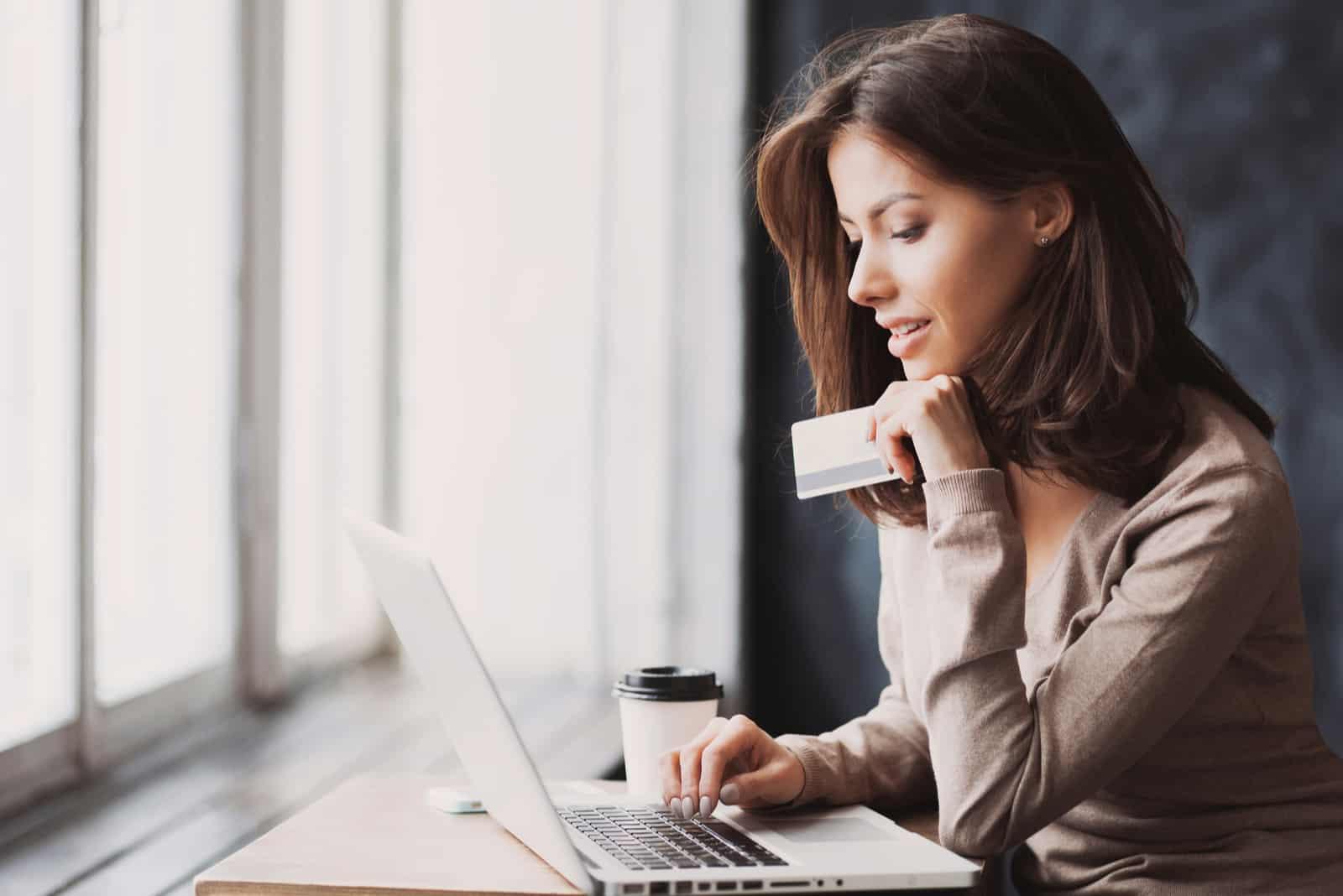Jeune femme, tenue, carte crédit, et, utilisation ordinateur portable