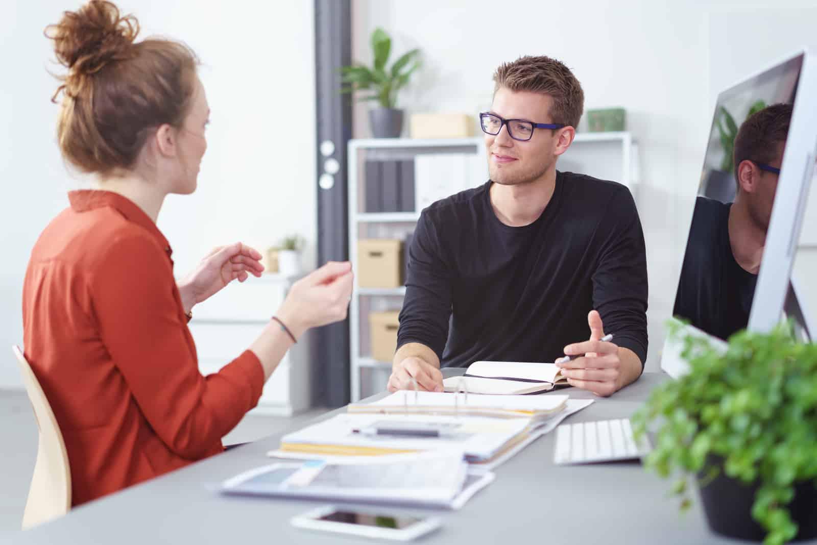 Jeune homme d'affaires et femme lors d'une réunion ayant une discussion animée
