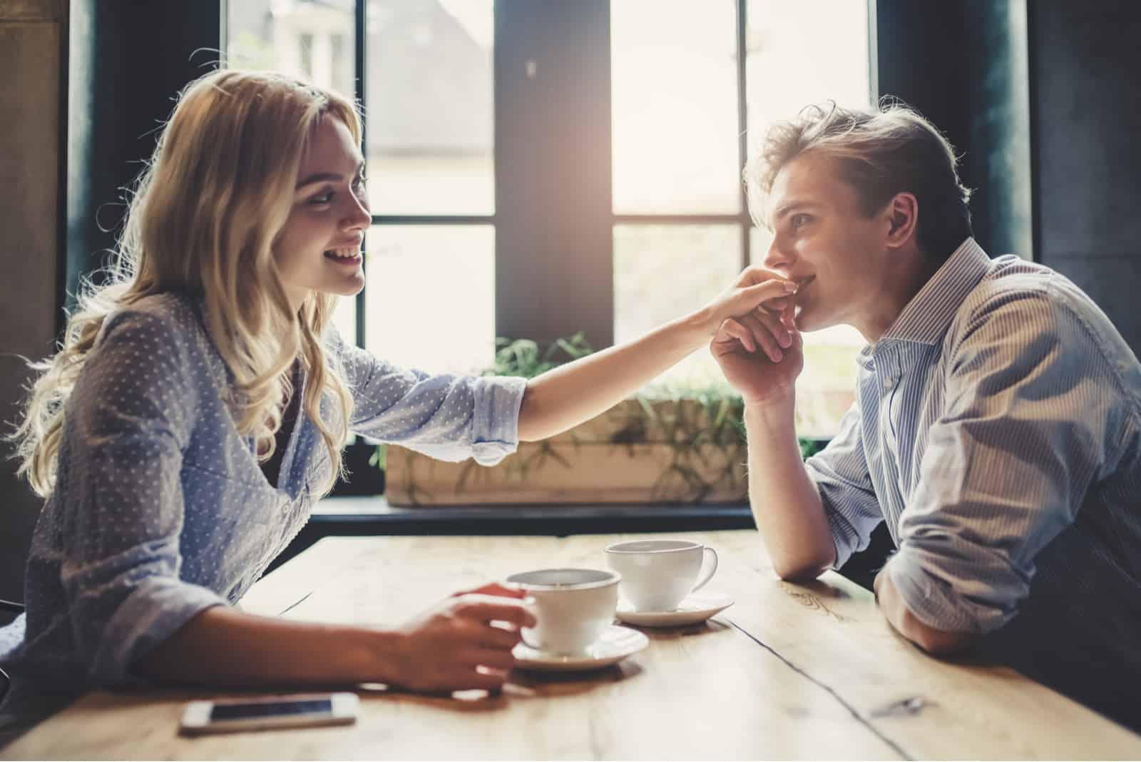 Jeune homme embrasse la main de la femme à la date au café