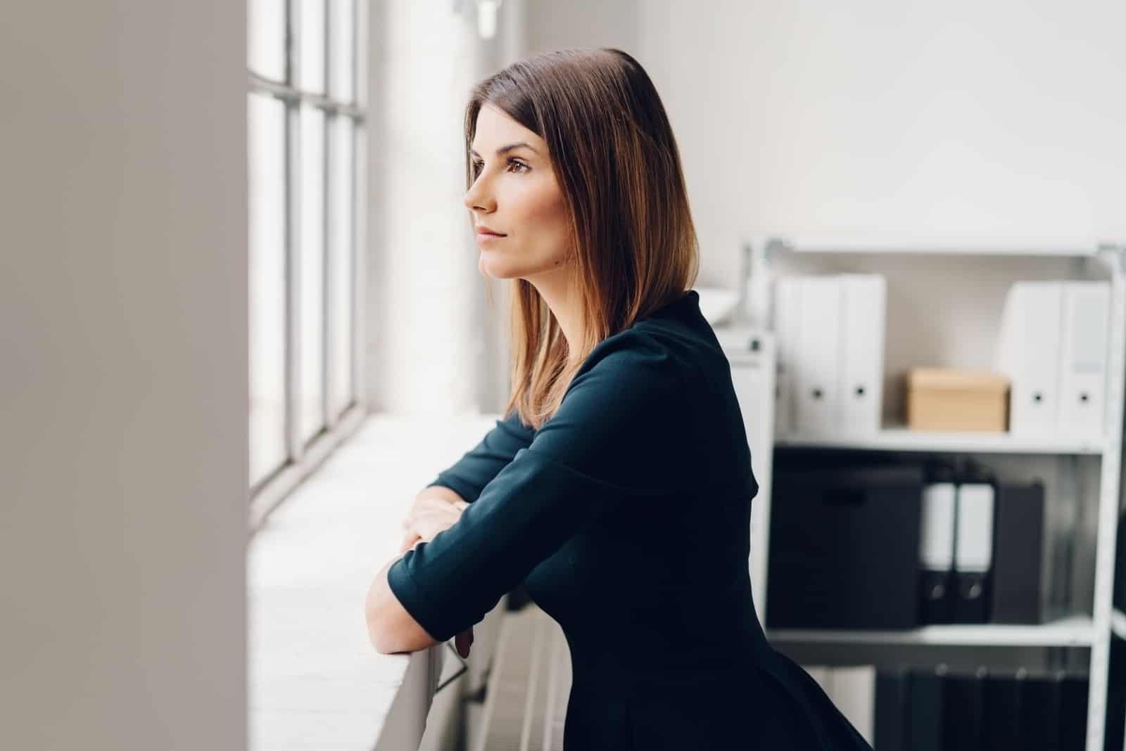 Jolie femme debout regardant par une fenêtre