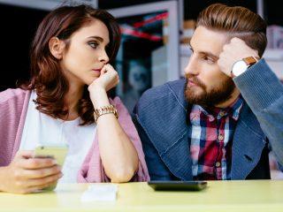 un homme et une femme s'assoient l'un à côté de l'autre et se regardent