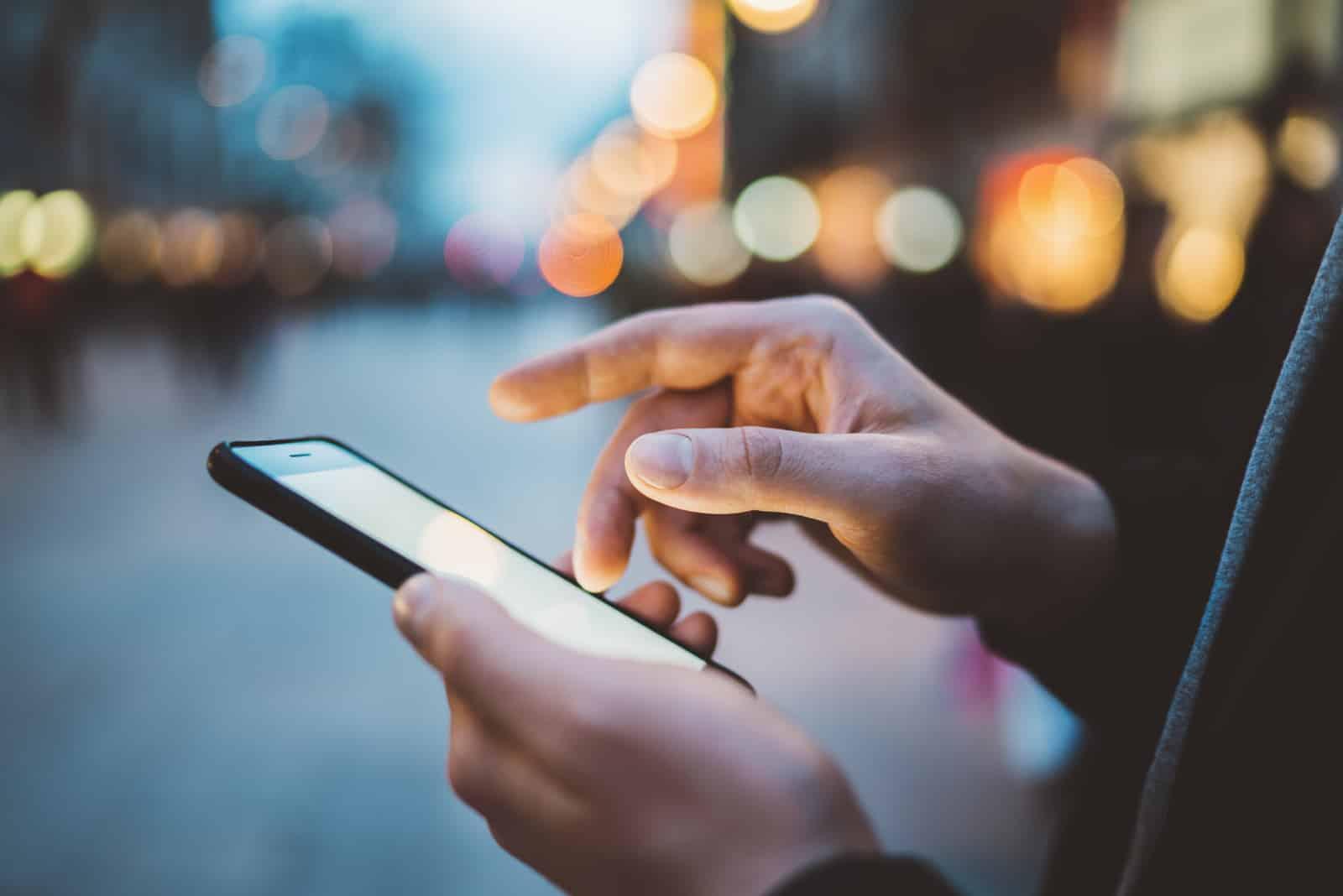 Mains mâles à l'aide de smartphone la nuit sur la rue commerçante de la ville
