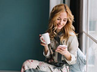 Une belle femme aux longs cheveux blonds est assise près de la fenêtre tenant une tasse et un bouton sur le téléphone