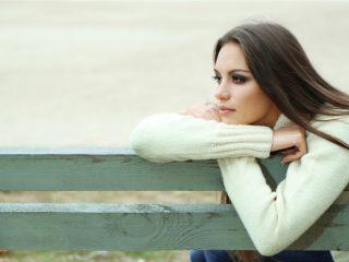une femme triste assise sur un banc de parc