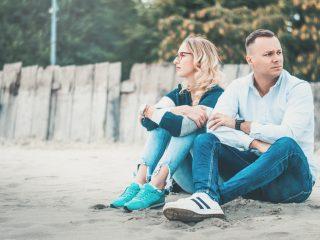 un homme et une femme sont assis sur la plage