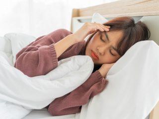 la femme est allongée dans son lit et tient sa tête