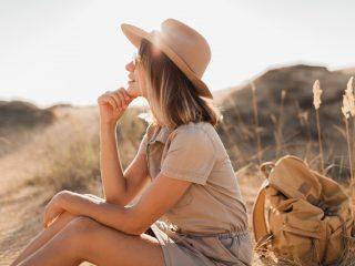 une belle femme avec un chapeau sur la tête est assise