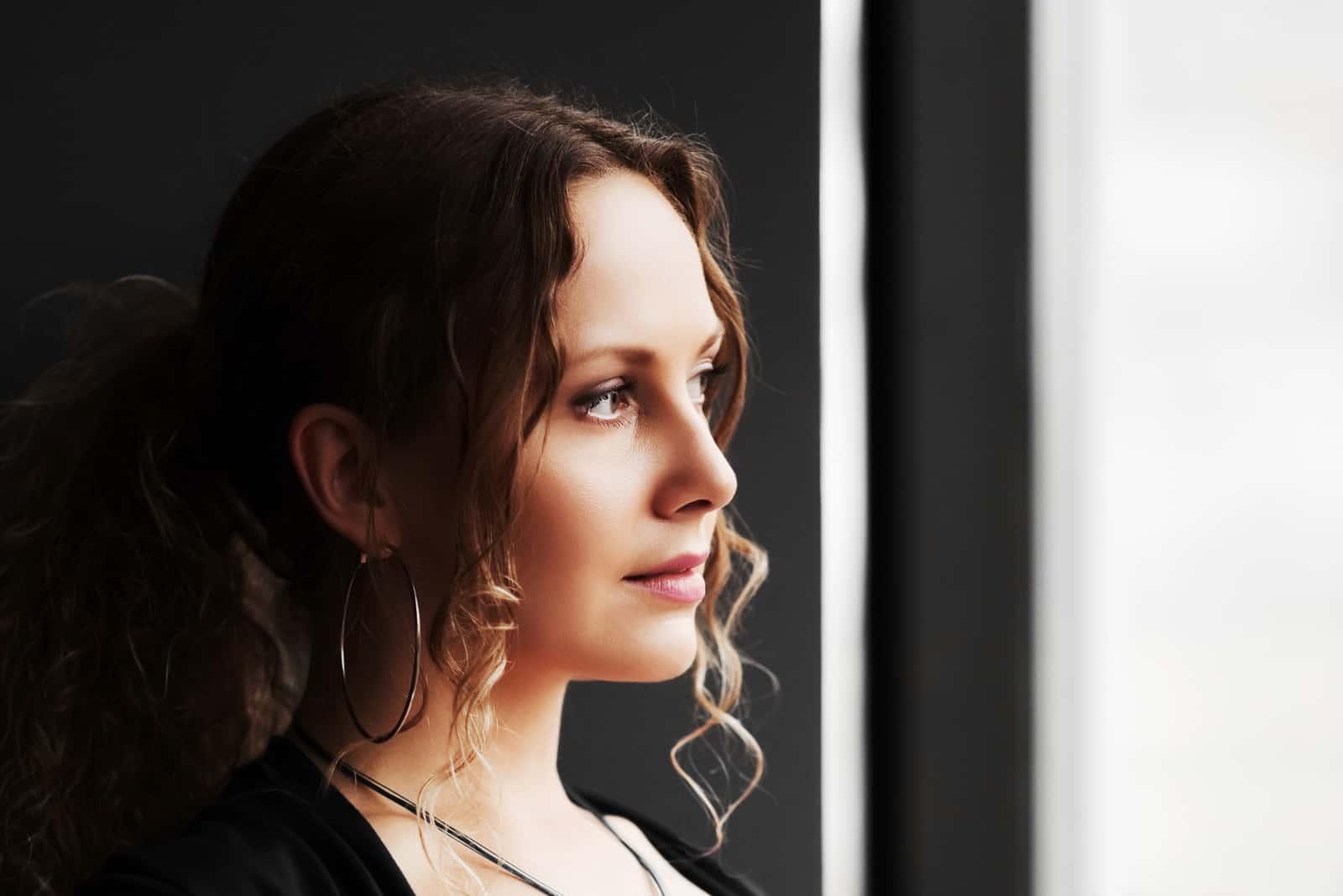 Triste belle femme regardant par la fenêtre