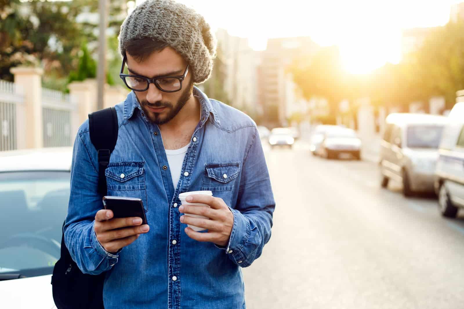 Un homme debout dans la rue tenant un téléphone et une tasse de sel de café à la main