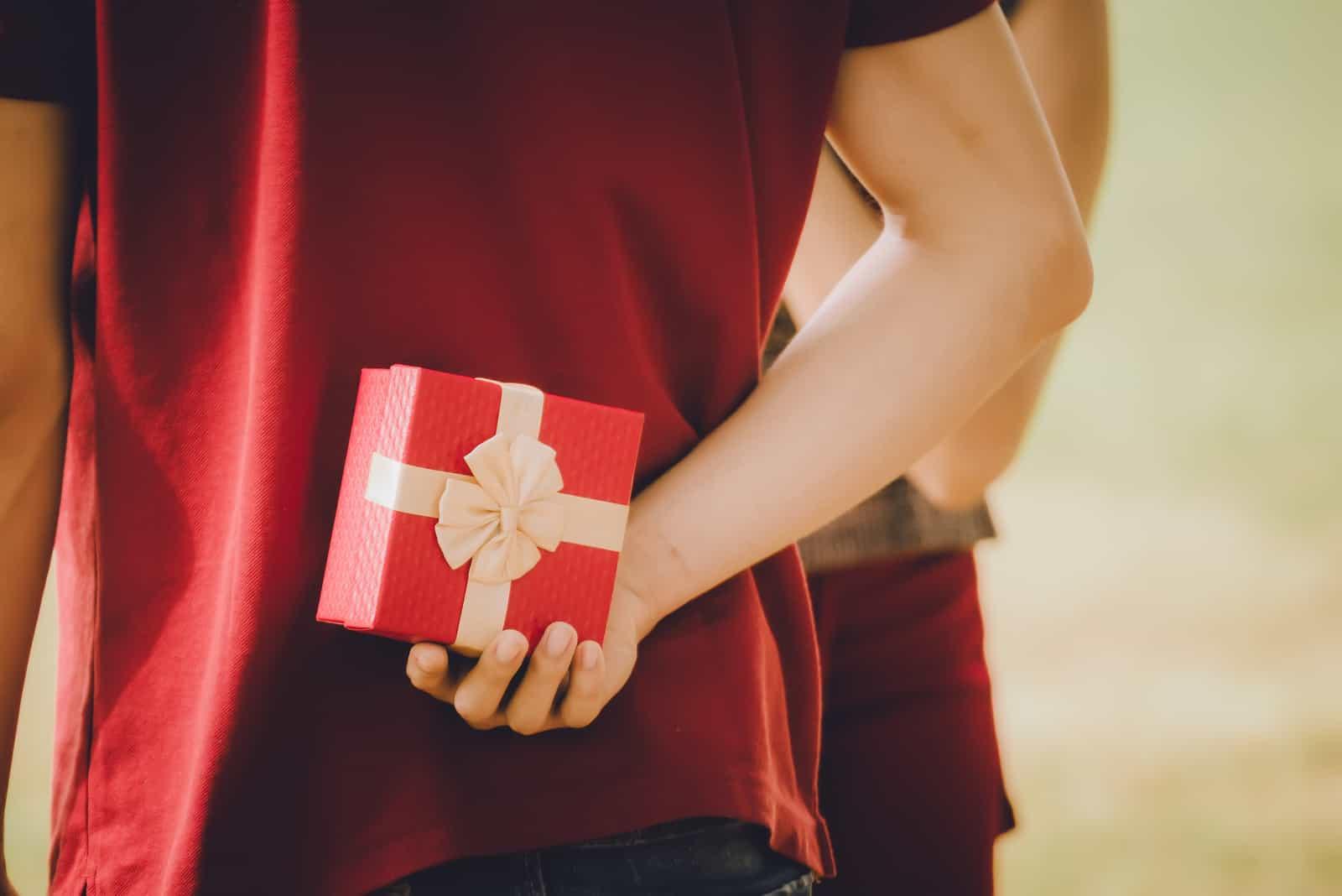 Un homme tenant une boîte-cadeau pour petite amie surprise
