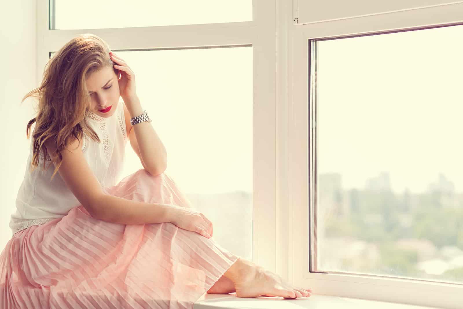Une belle femme aux longs cheveux bruns est assise près de la fenêtre, les yeux baissés