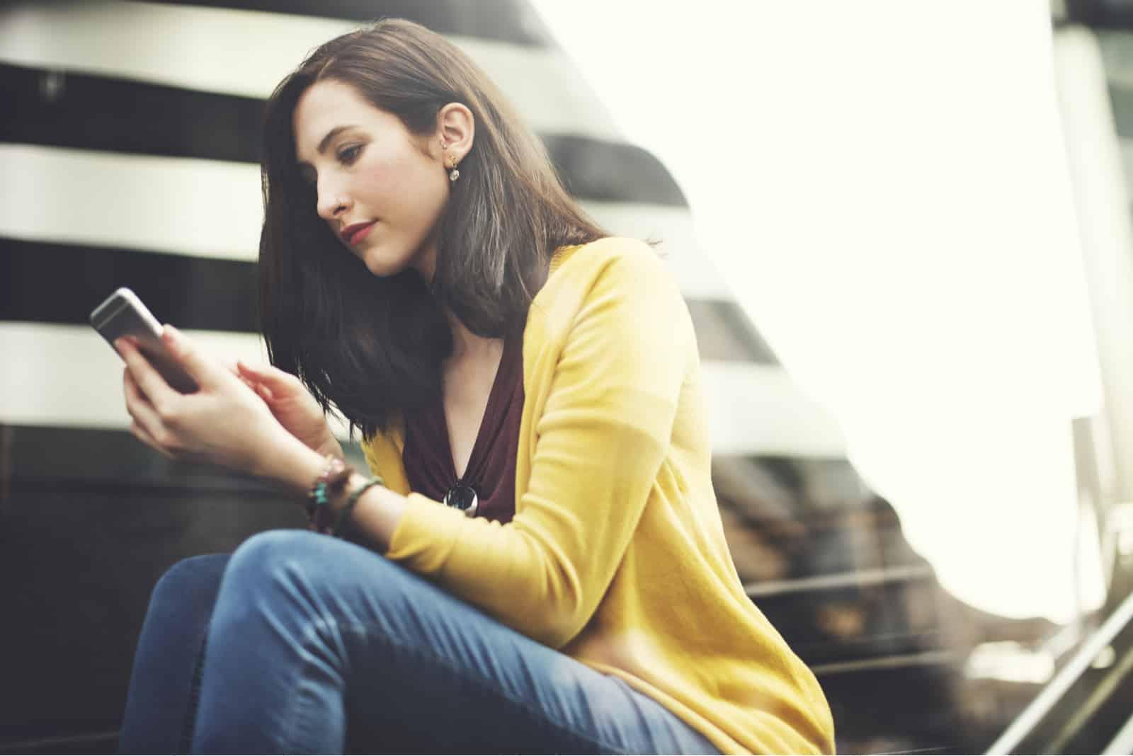 Une femme aux cheveux bruns dans une veste jaune est assise et des boutons sur le téléphone