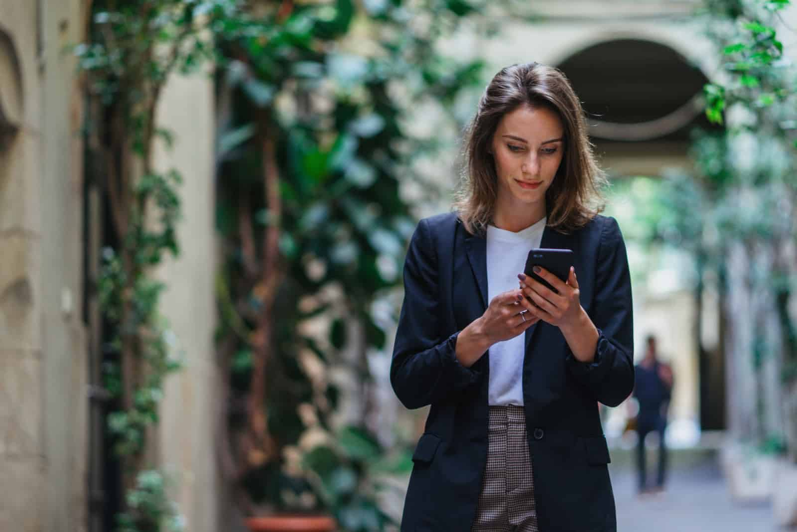 Une femme aux cheveux bruns debout dans la rue et en appuyant sur un téléphone