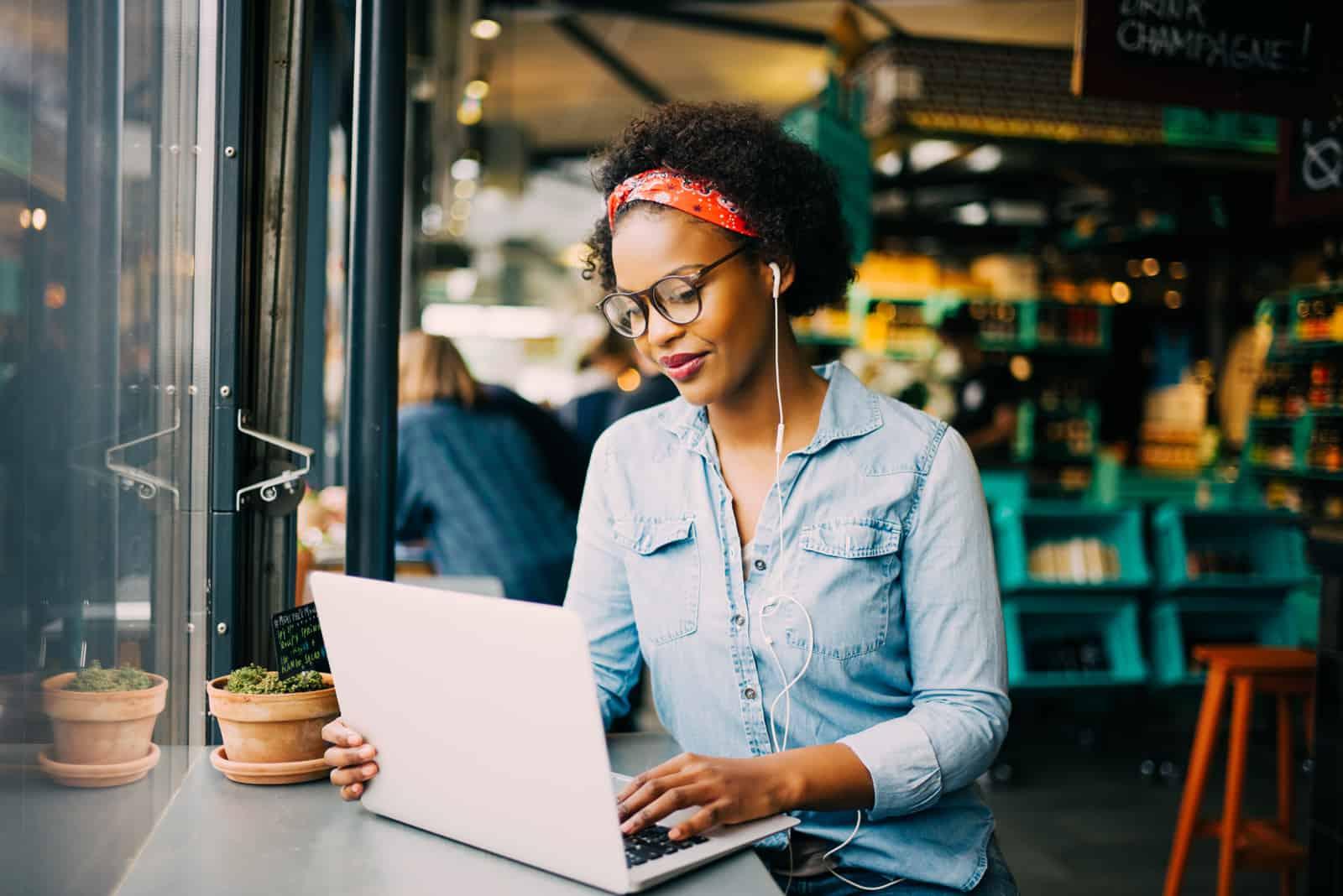Une femme aux cheveux crépus est assise dans un café derrière un ordinateur portable