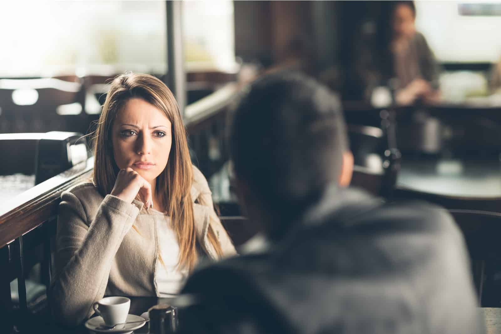 Une femme aux longs cheveux blonds a l'air confus à l'homme pendant qu'ils parlent