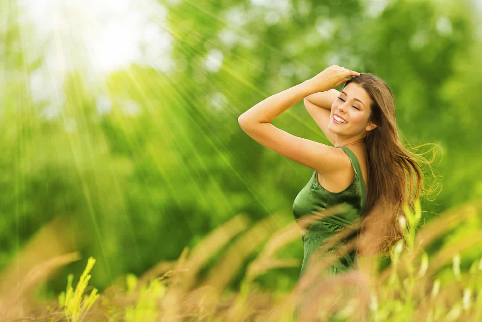 Une femme aux longs cheveux bruns dans une robe verte est assise dans un champ et rit