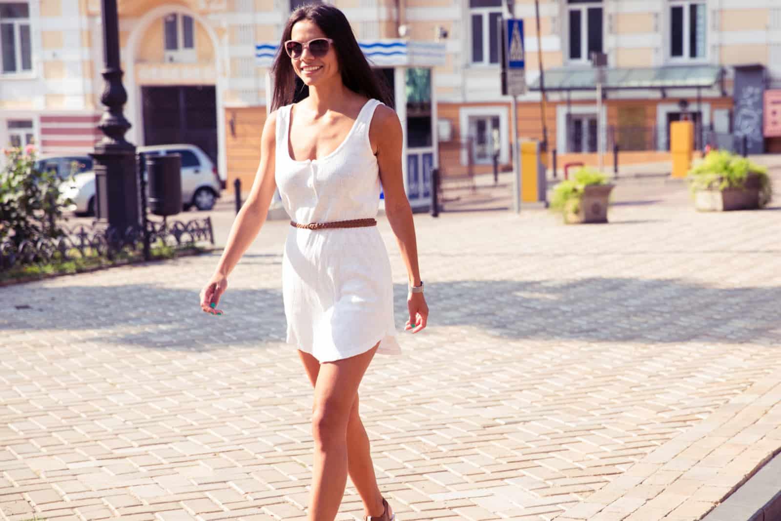Une femme aux longs cheveux noirs dans une robe blanche marche dans la rue