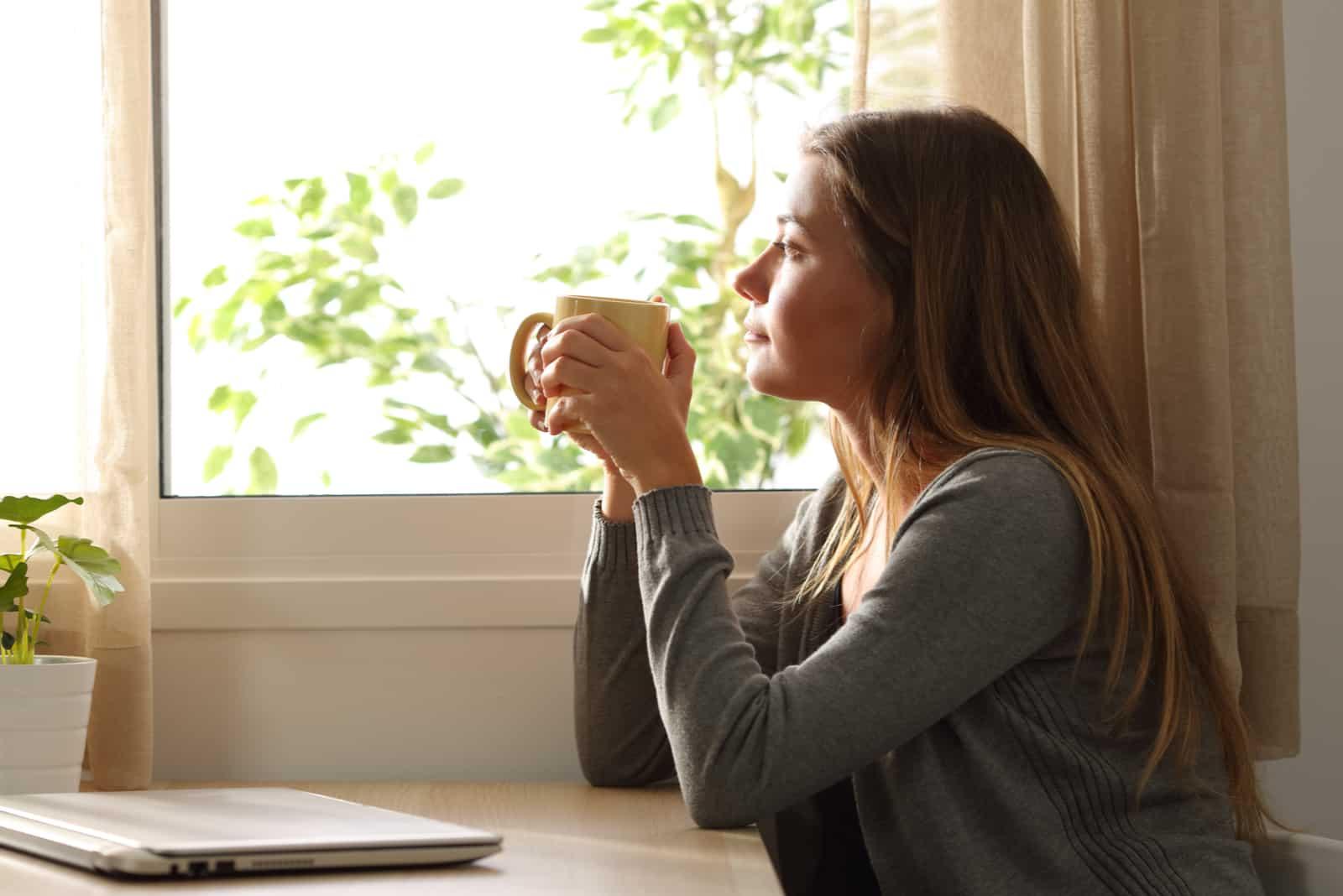 Une femme imaginaire aux longs cheveux blonds tient une tasse à la main et regarde par la fenêtre