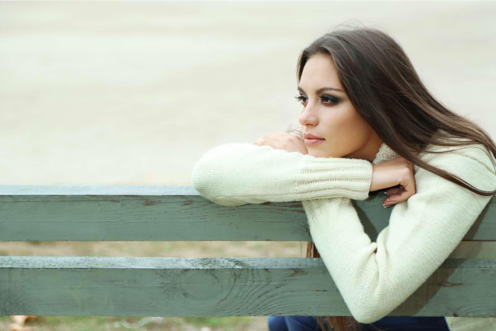 Une femme imaginaire est assise appuyée contre un banc de parc