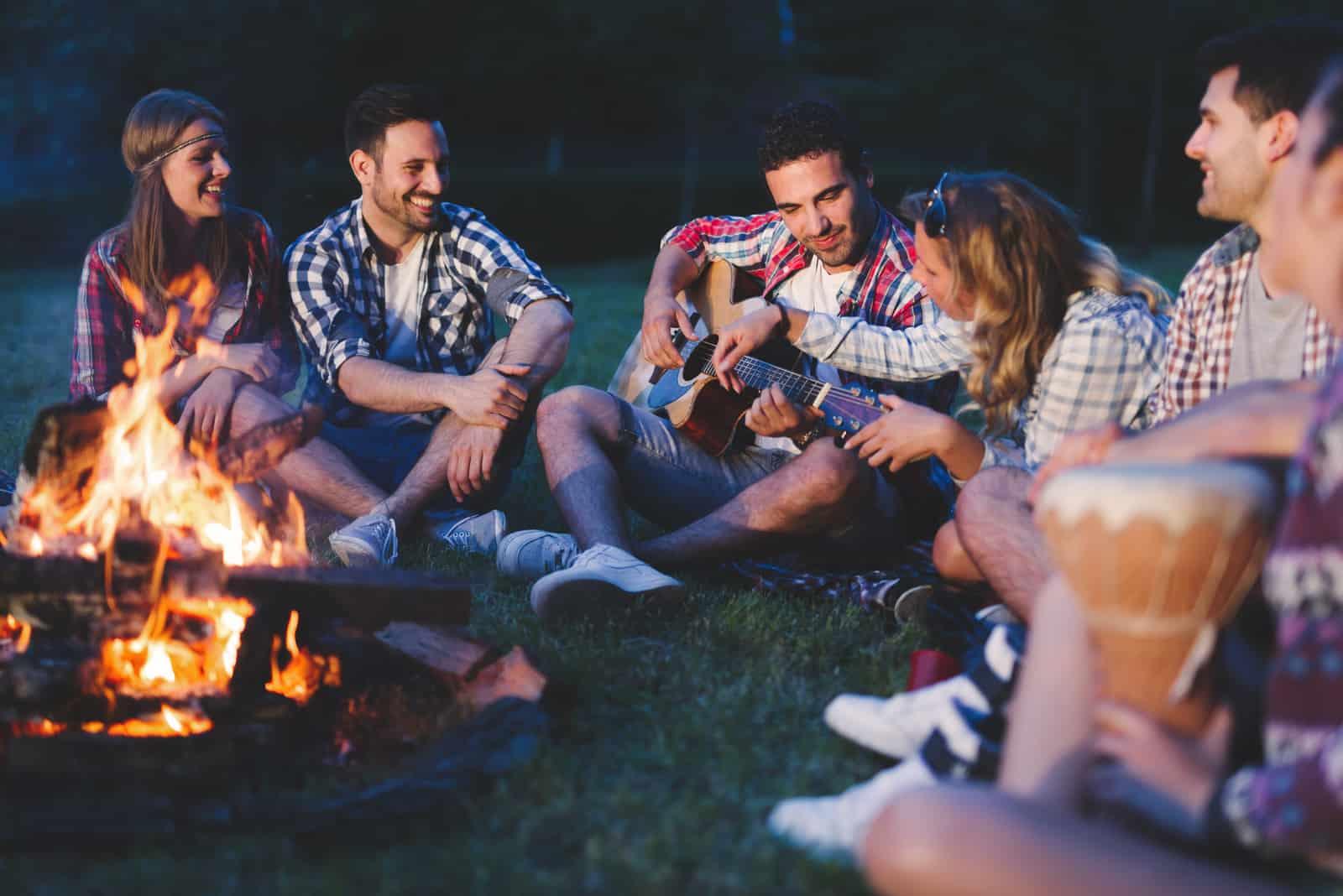 amis jouant de la musique et profitant d'un feu de joie dans la nature