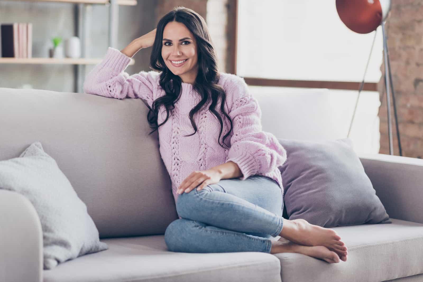 belle femme assise sur le canapé à la maison