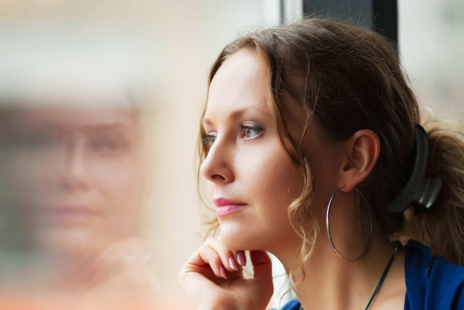 belle femme regardant à travers une fenêtre