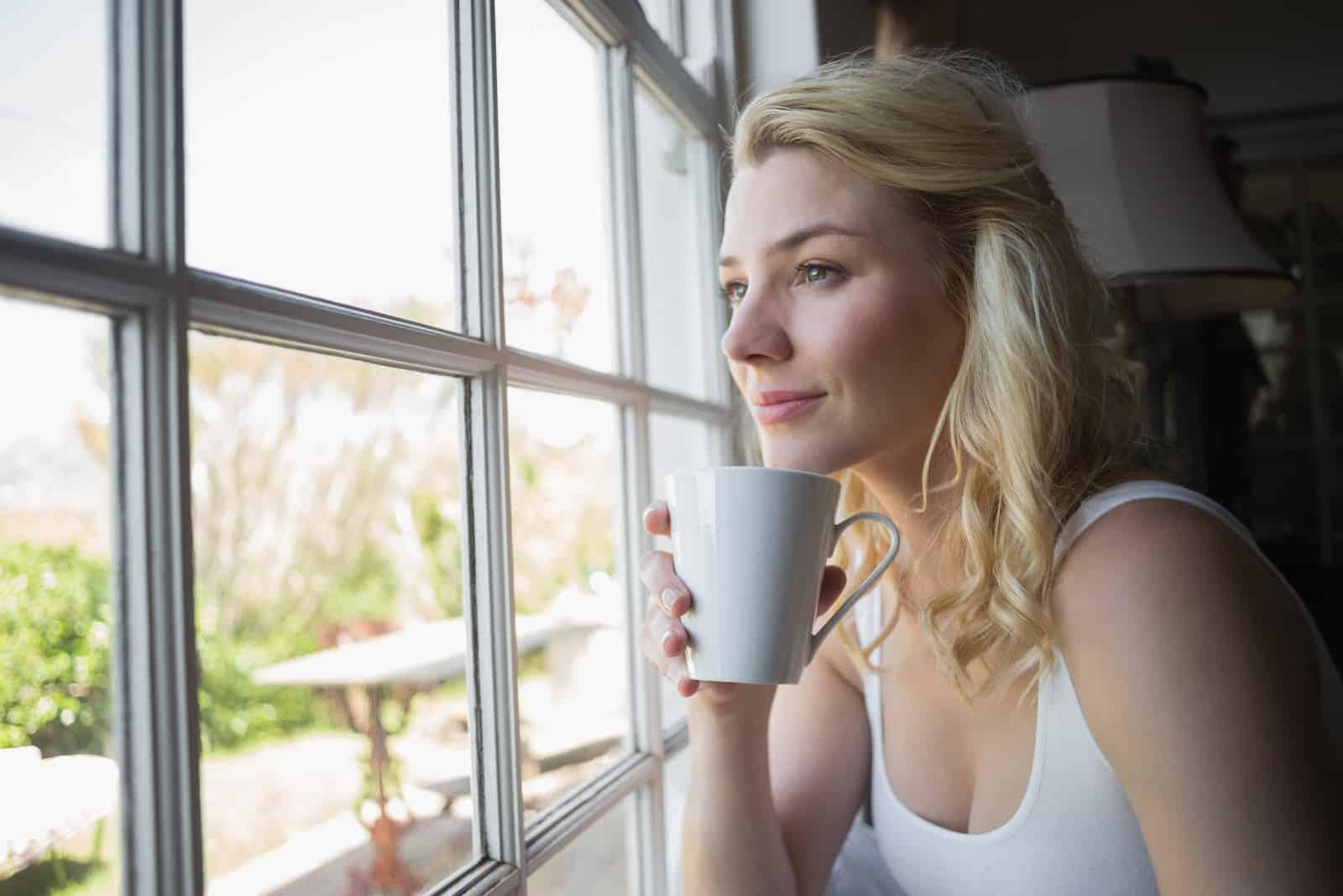 blonde assise près de la fenêtre en train de prendre un café