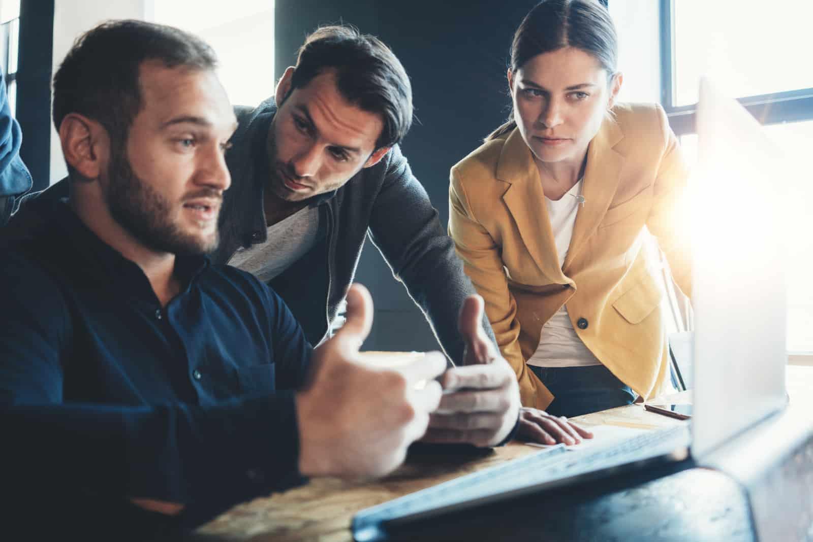 collègues de travail parlant sur un ordinateur portable