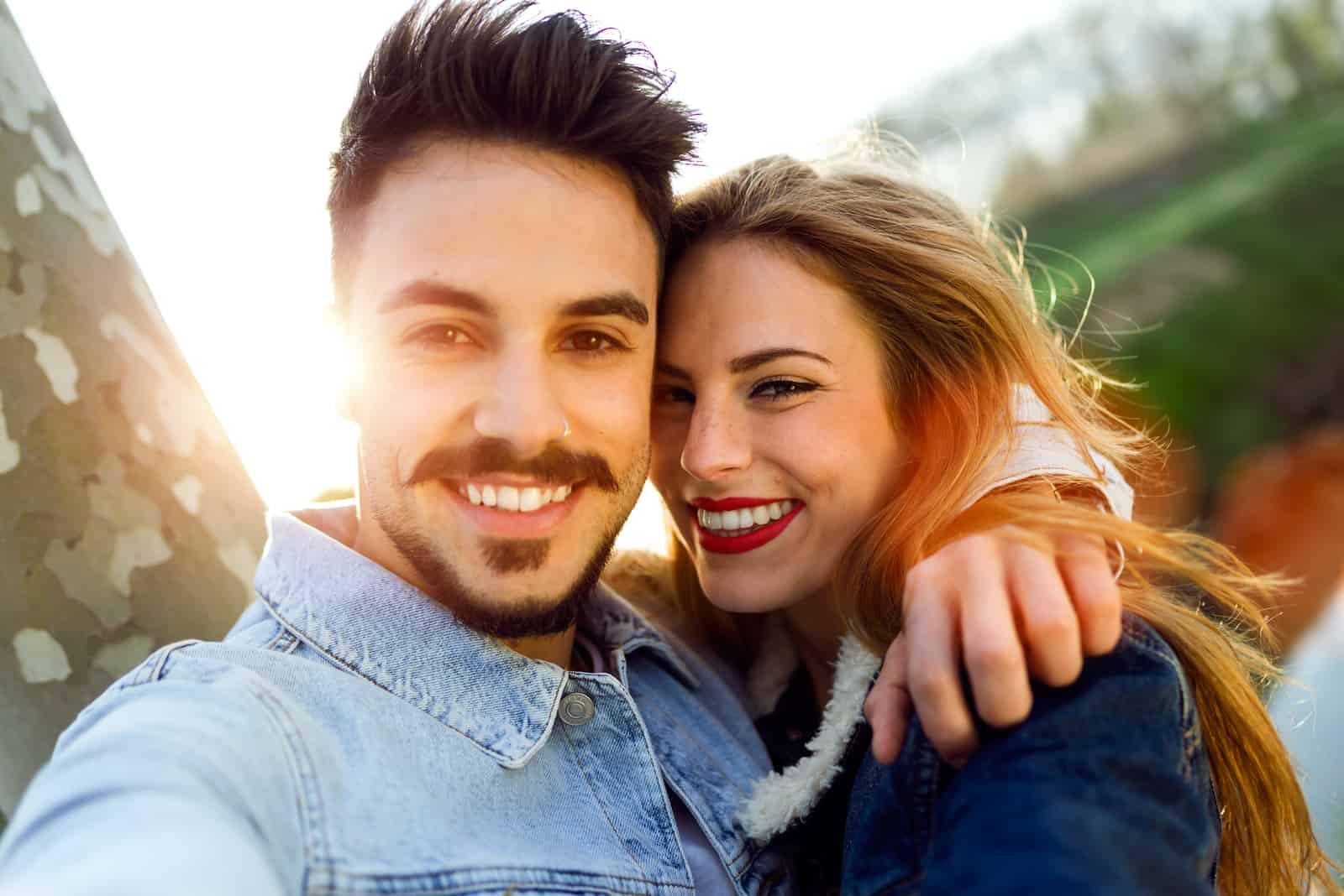 couple souriant posant dans un câlin en plein air