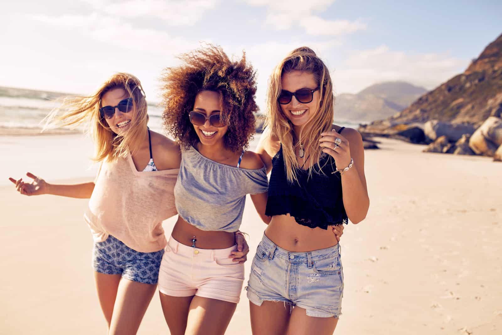 des amis marchent le long de la plage en s'embrassant et en riant