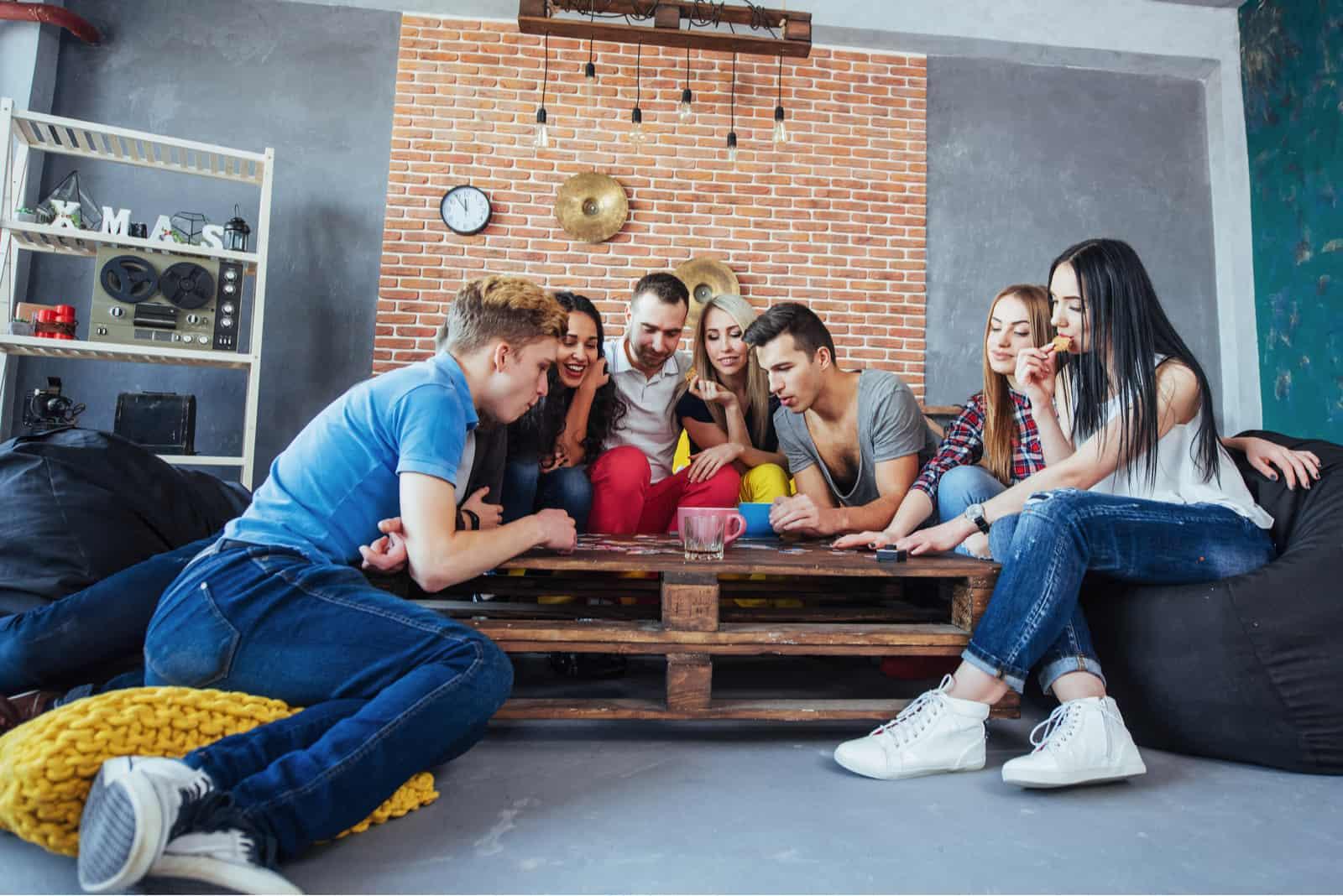 des amis s'assoient à une table et jouent à un jeu
