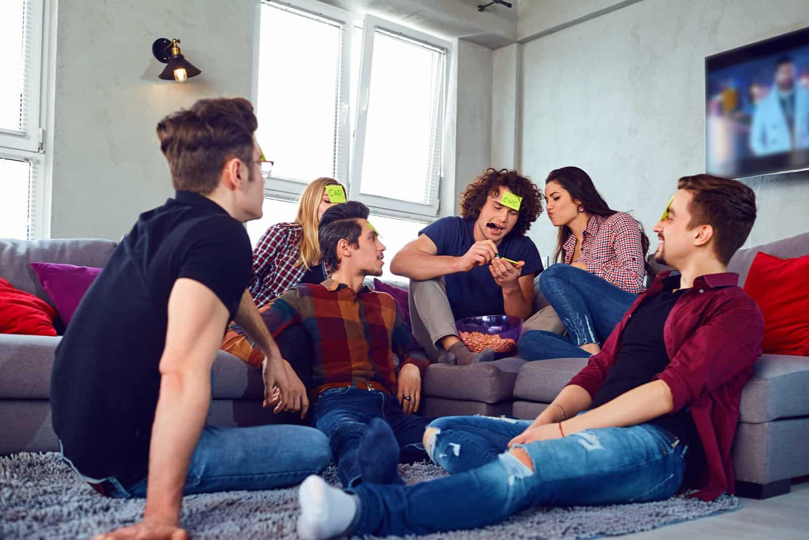 des amis s'assoient par terre et jouent à un jeu