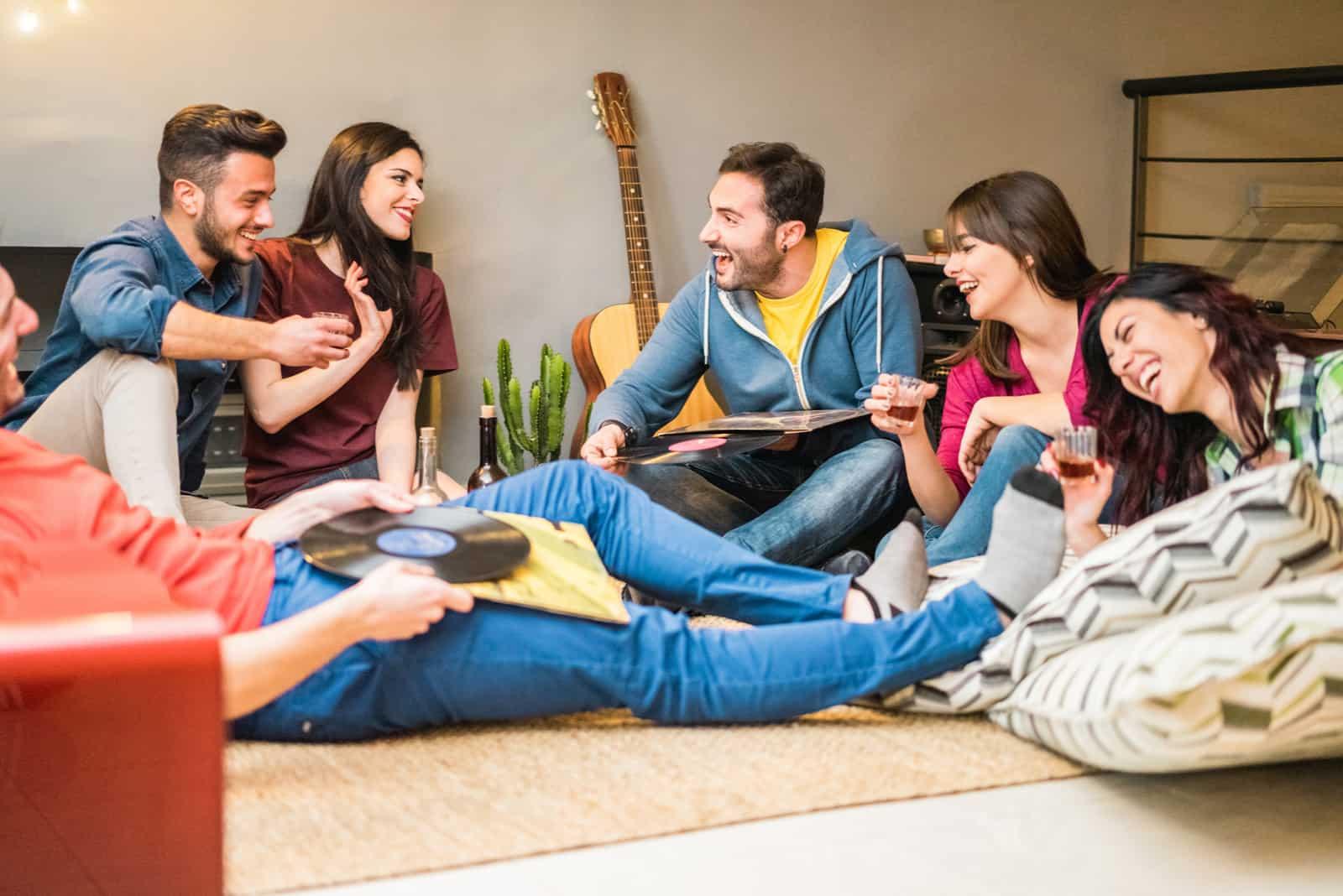des amis sont assis sur le sol en tenant des planches et en riant