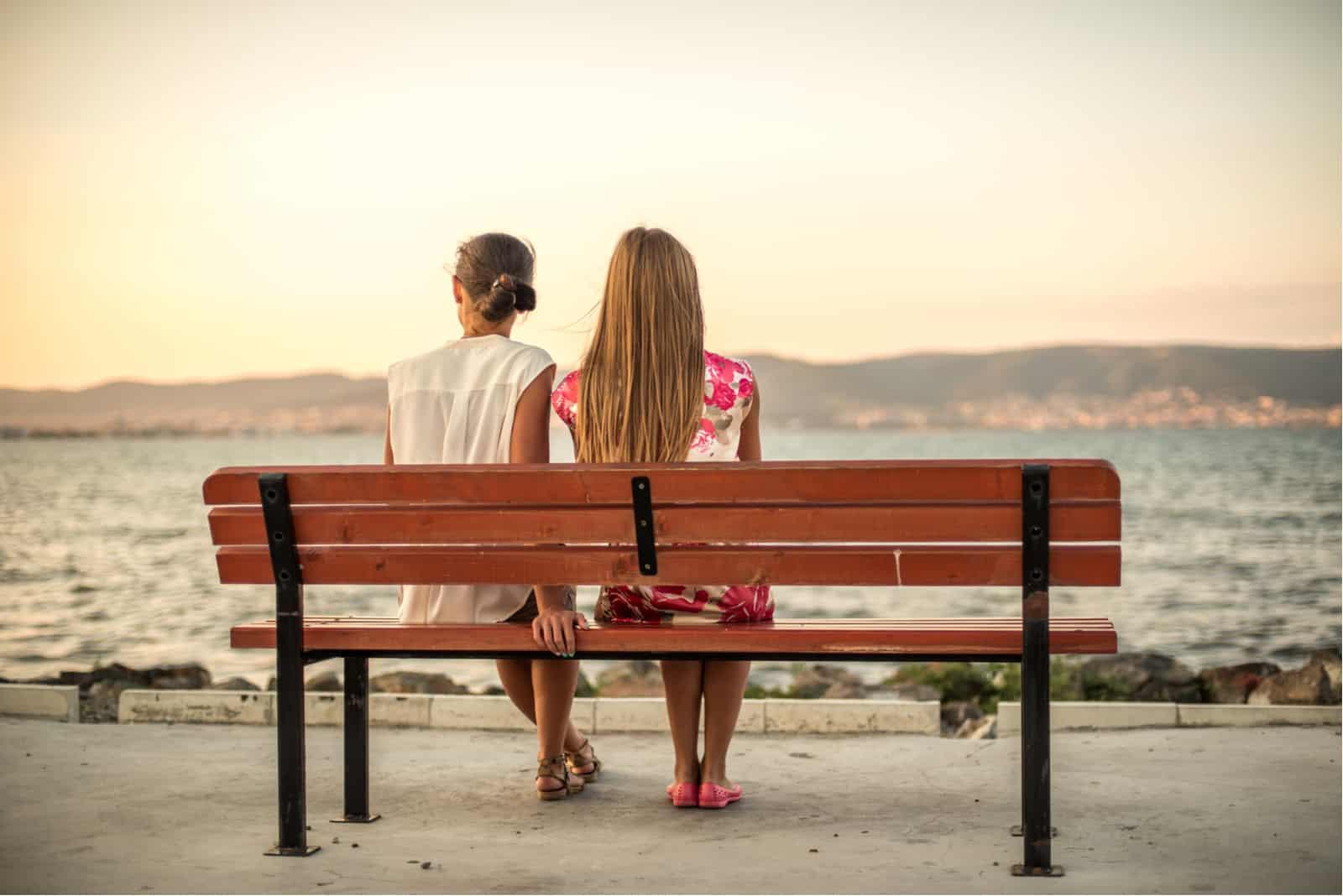 deux amis assis sur un banc en bois