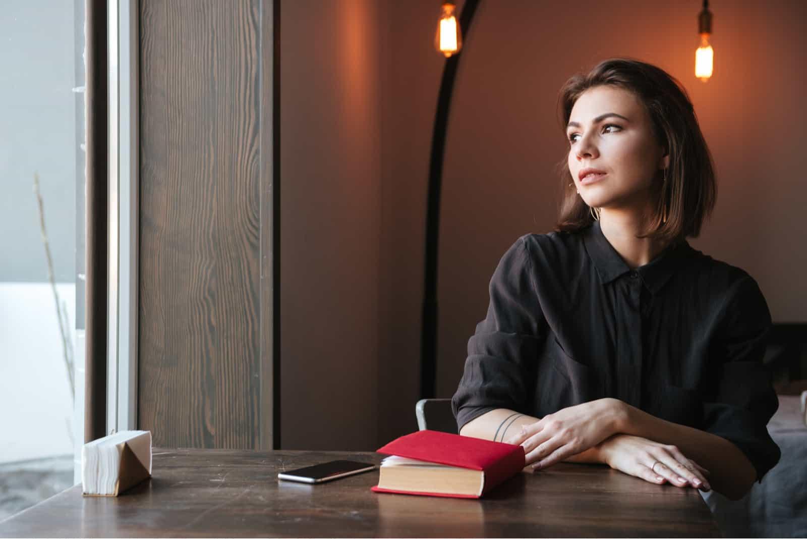 femme assise à la table près de livre et téléphone au café