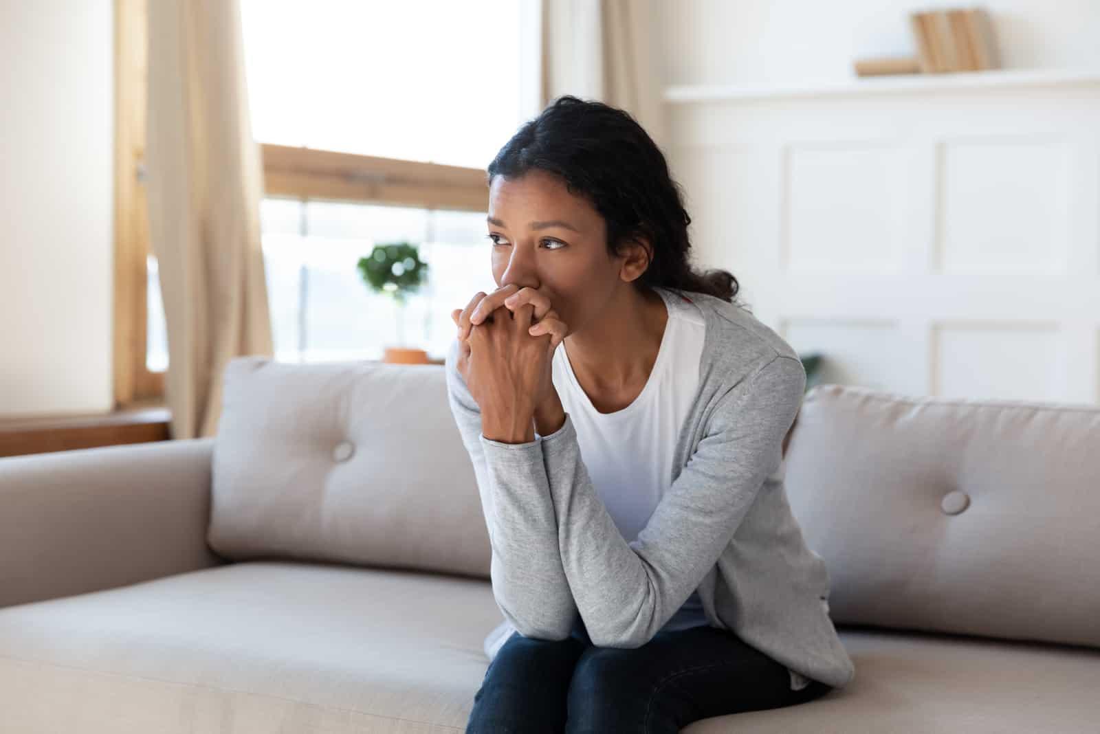 femme assise sur le canapé à la maison regarder à distance