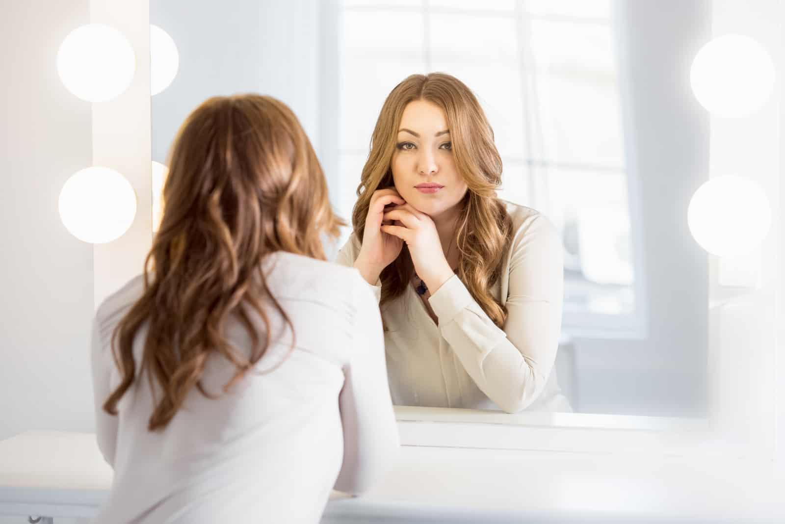 femme élégante aux cheveux bouclés regardant la réflexion dans le miroir