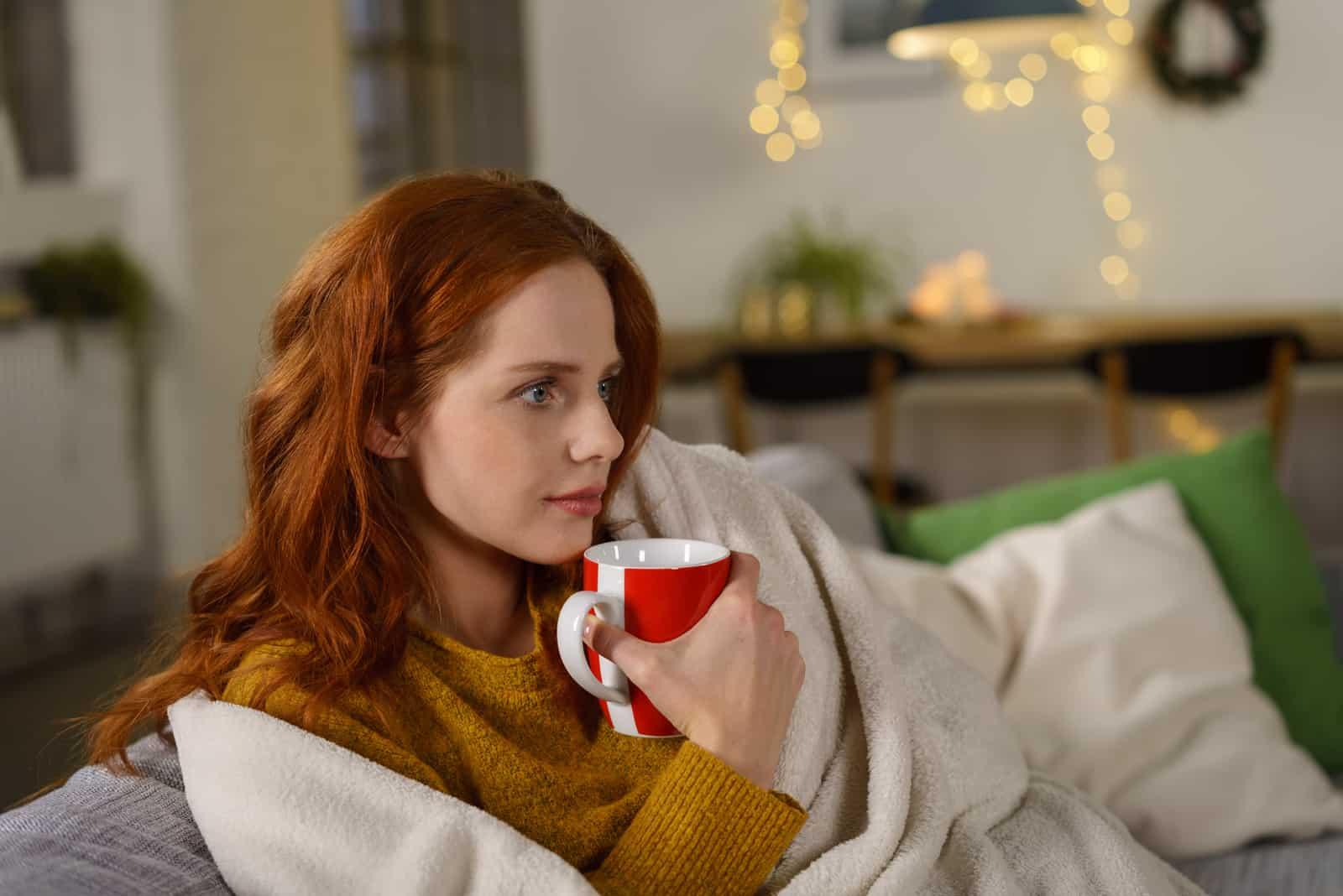 femme rousse assise sur un canapé à la maison
