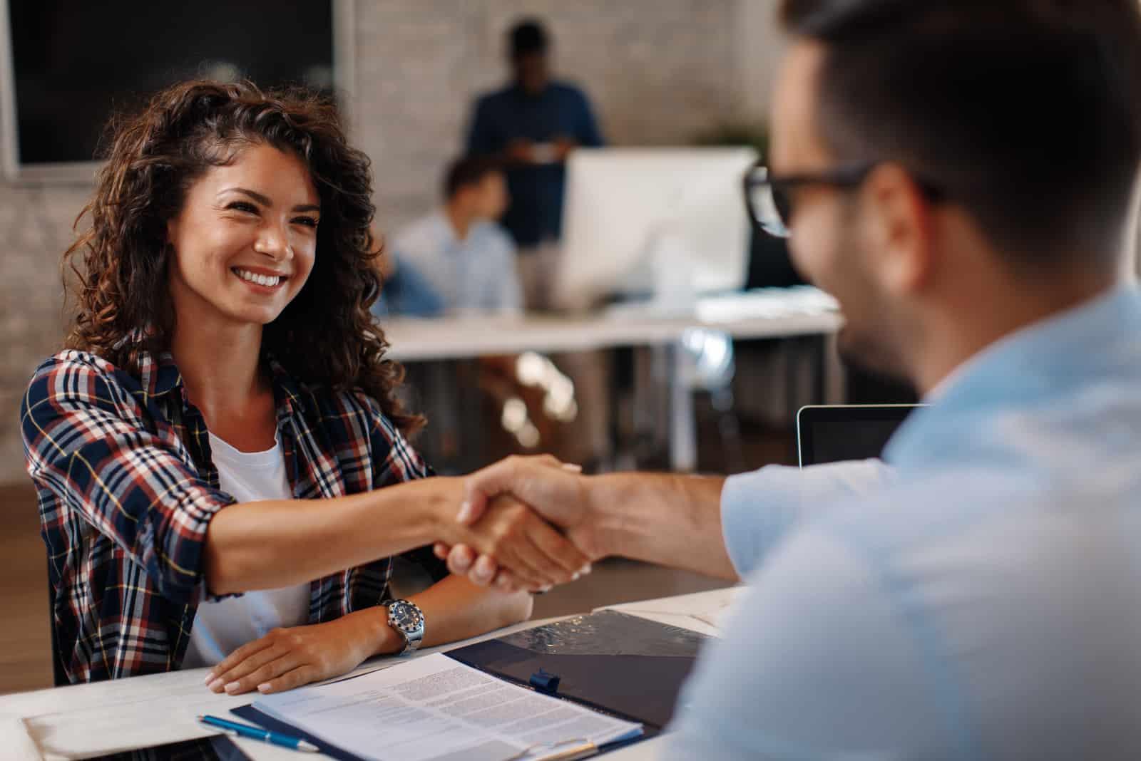 femme signant des contrats et poignée de main avec un gestionnaire