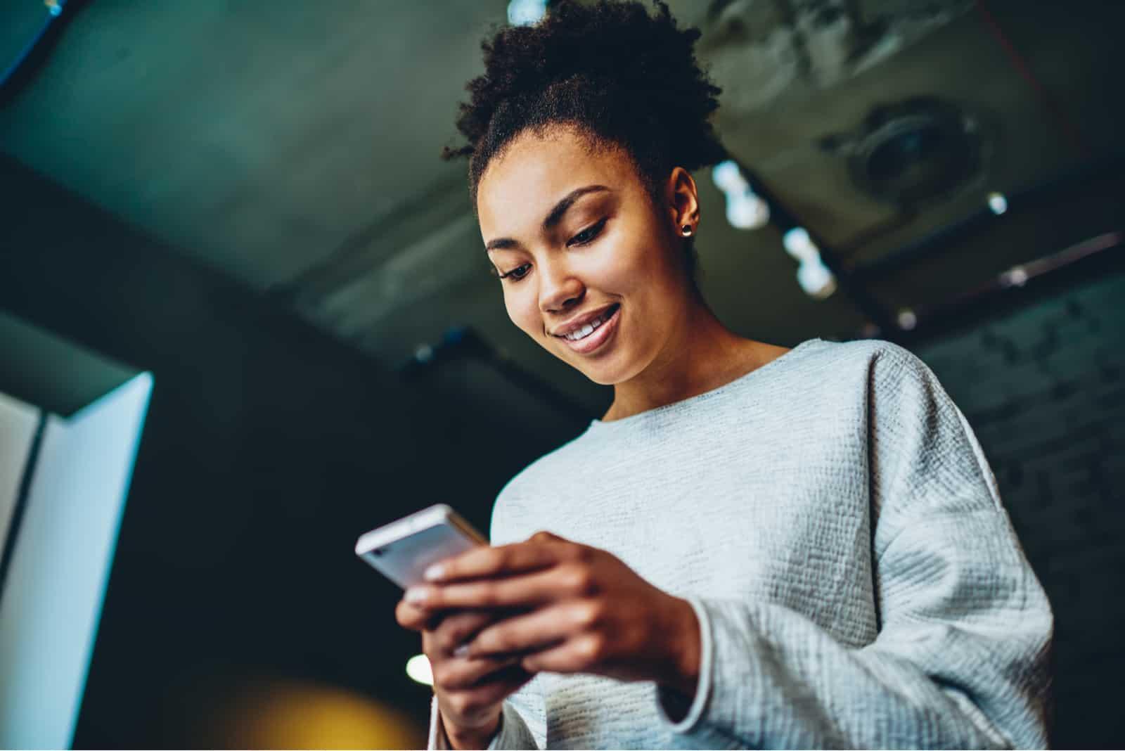 femme souriante tout en utilisant son téléphone