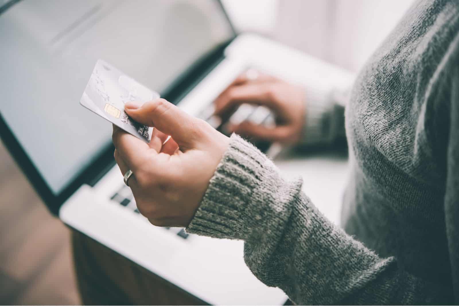 femme tenant une carte de crédit alors qu'il était assis par ordinateur portable