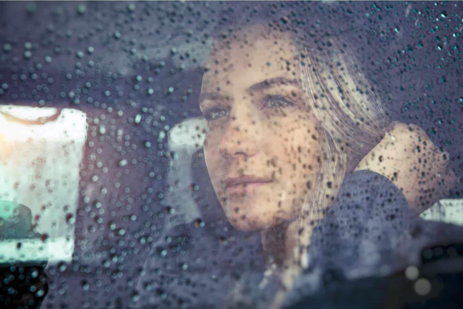 femme triste assise dans la voiture par temps pluvieux
